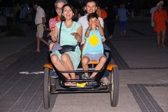 Group of friends riding a quadricycle together in the evening stock image