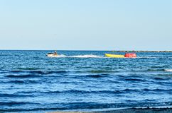 Man riding a jet ski over blue Black Sea water, banana boat. Royalty Free Stock Images