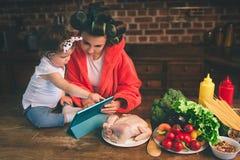 Maman à la maison Jeune mère avec le petit enfant dans la cuisine à la maison Femme faisant beaucoup de tâches tandis que s'occup Image stock