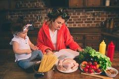 Maman à la maison Jeune mère avec le petit enfant dans la cuisine à la maison Femme faisant beaucoup de tâches tandis que s'occup Images libres de droits