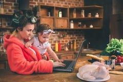 Maman à la maison Jeune mère avec le petit enfant dans la cuisine à la maison Femme faisant beaucoup de tâches tandis que s'occup Images stock