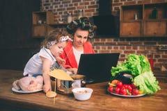 Maman à la maison Jeune mère avec le petit enfant dans la cuisine à la maison Femme faisant beaucoup de tâches tandis que s'occup Photo stock