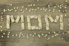MAMAN écrite avec des guimauves Concept de jour du ` s de mère vacances de ressort Sur le fond en bois Photos libres de droits