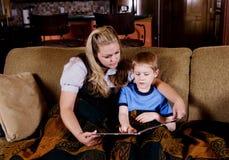 Maman affichant un livre à son enfant image libre de droits