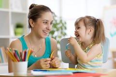 Maman aidant son enfant à travailler le papier coloré Image stock