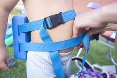 Maman ajustant la ceinture de flotteur de deux ans de petit garçon Photo stock