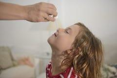 Maman appliquant des baisses de nez Photo stock