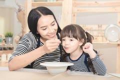 Maman asiatique alimentant le petit déjeuner sain à sa fille mignonne Photo libre de droits