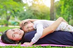 Maman asiatique heureuse embrasser sa fille se situant dans le jardin vert avec regarder la caméra photo stock