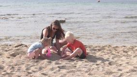 Maman avec des enfants jouant sur la plage banque de vidéos