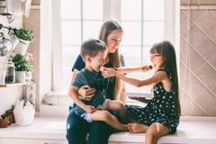 Maman avec des enfants mangeant sur la table de cuisine photo stock