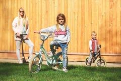 Maman avec des enfants sur des bicyclettes Image stock