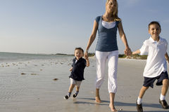 Maman avec des gosses sur une plage Image stock