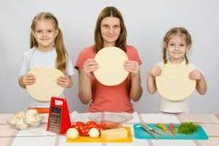 Maman avec deux petites filles s'asseyant dans une rangée aux bases tenues dans la main de table de cuisine et d'une pizza Photos libres de droits