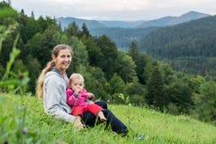 Maman avec l'enfant sur le fond des montagnes images stock