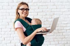 Maman avec l'ordinateur portable jugeant nouveau-né dans la bride de bébé photo libre de droits