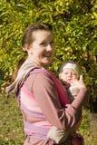 Maman avec la chéri dans l'élingue image libre de droits
