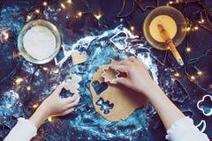 Maman avec la fille coupant les symboles de Noël dans la pâte Photographie stock libre de droits