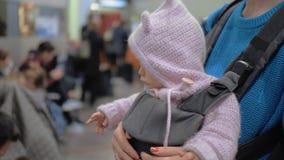 Maman avec la fille de bébé dans le transporteur de kangourou à l'aéroport clips vidéos