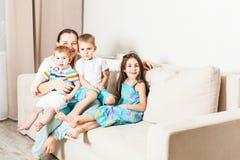 Maman avec la fille et deux fils à la maison photo stock