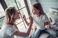 Maman avec la fille faisant le maquillage Image stock