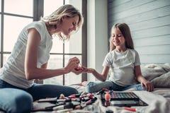 Maman avec la fille faisant le maquillage Photo libre de droits
