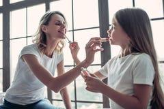 Maman avec la fille faisant le maquillage Photographie stock