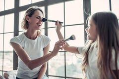 Maman avec la fille faisant le maquillage Image libre de droits
