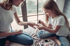 Maman avec la fille faisant le maquillage Photographie stock libre de droits