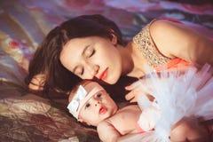 Maman avec la fille sur le lit Photographie stock libre de droits