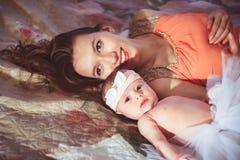 Maman avec la fille sur le lit Photographie stock