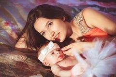 Maman avec la fille sur le lit Photos stock