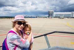 Maman avec la petite fille à l'aéroport Photos stock