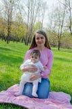Maman avec le bébé dans des vêtements lumineux sur un plaid rose sur la droite verte Famille se reposant en parc un jour chaud images libres de droits