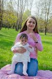 Maman avec le b?b? dans des v?tements lumineux sur un plaid rose sur la droite verte Famille se reposant en parc un jour chaud photo stock