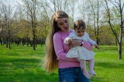 Maman avec le b?b? dans des v?tements lumineux sur un plaid rose sur la droite verte Famille se reposant en parc un jour chaud images libres de droits