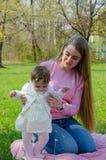 Maman avec le b?b? dans des v?tements lumineux sur un plaid rose sur la droite verte Famille se reposant en parc un jour chaud image libre de droits