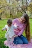 Maman avec le b?b? dans des v?tements lumineux sur un plaid rose sur la droite verte Famille se reposant en parc un jour chaud photo libre de droits