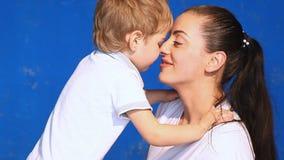 Maman avec le baiser de caresse de jeu de petit garçon dans la chambre clips vidéos