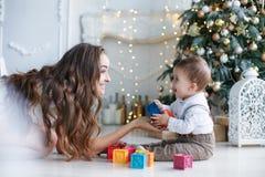 Maman avec le petit fils jouant avec les blocs colorés près de l'arbre de Noël Photographie stock