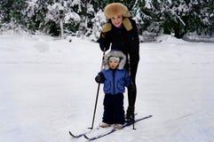 Maman avec le petit fils sur des skis Photographie stock