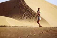 Maman avec le soleil dans un désert Images libres de droits