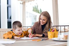 Maman avec les crayons colorés par aspiration de garçon Images stock