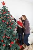 Maman avec son fils mettant des ornements sur l'arbre de Noël Image libre de droits
