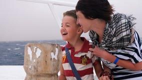 Maman avec son petit fils sur l'arc du bateau pendant une tempête et un vent violent banque de vidéos