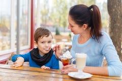 Maman avec un enfant dans un café mangeant le dessert images stock