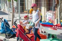 Maman avec un enfant sur une attraction du ` s d'enfants au centre de Pomorie, Bulgarie Image stock