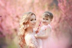 Maman avec un nourrisson dans la roseraie avec des arbres de fleurs photos stock
