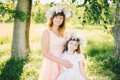 Maman avec un sourire attrayant étreignant sa fille en parc pendant l'été Photographie stock