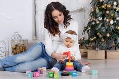 Maman avec une petite fille jouant le réveillon de Noël sur le fond d'un bel arbre de Noël Photos stock